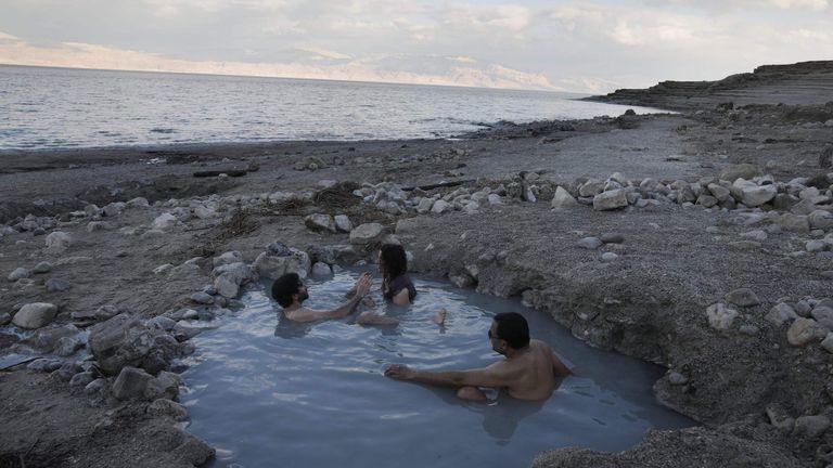 Tourists enjoy a spring water pool along the Dead Sea shore near Kibbutz Ein Gedi on April 2, 2017