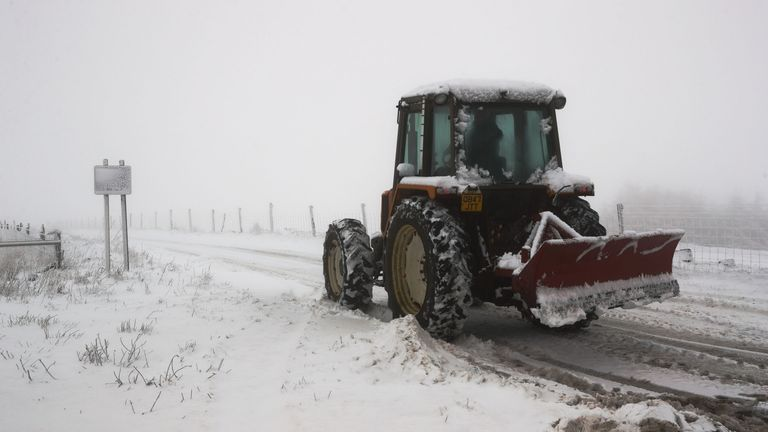 A tractor equipped with a snow plow clearing snow on the A53 near Buxton, Derbyshire