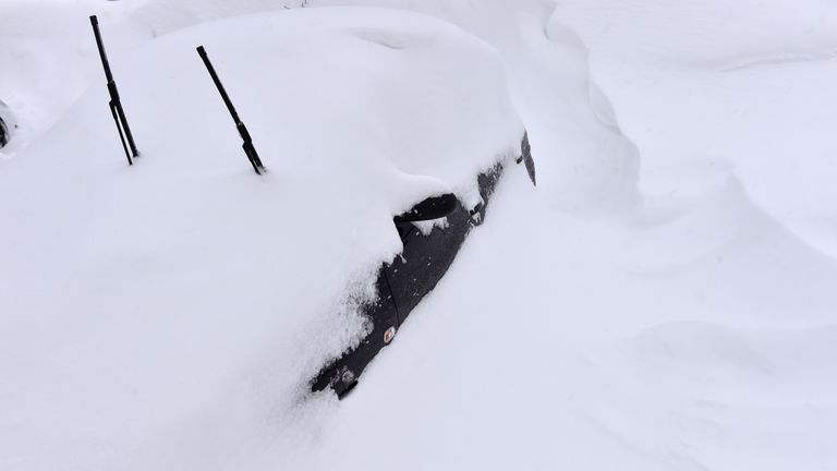 Cars have been left covered by a thick blanket of snow