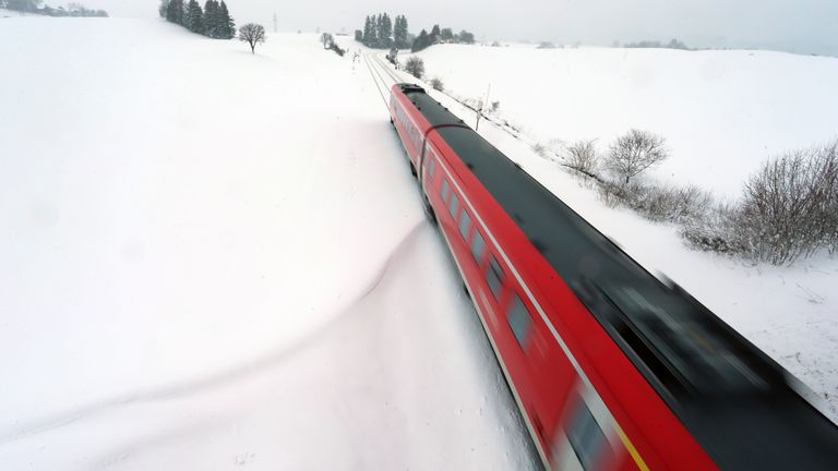 A train travels through the snow in Aitrang, southern Germany