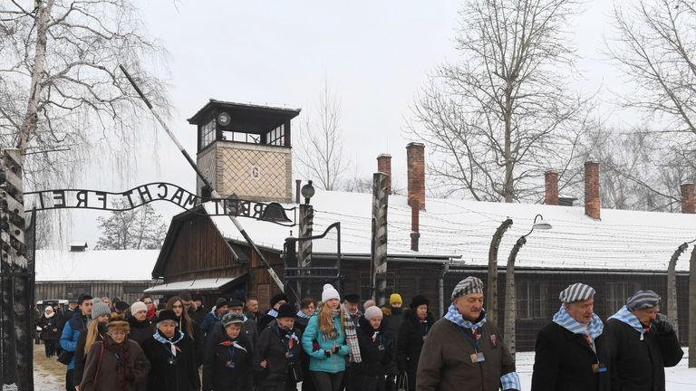 Former prisoners and officials pass the main gate of the Auschwitz concentration camp