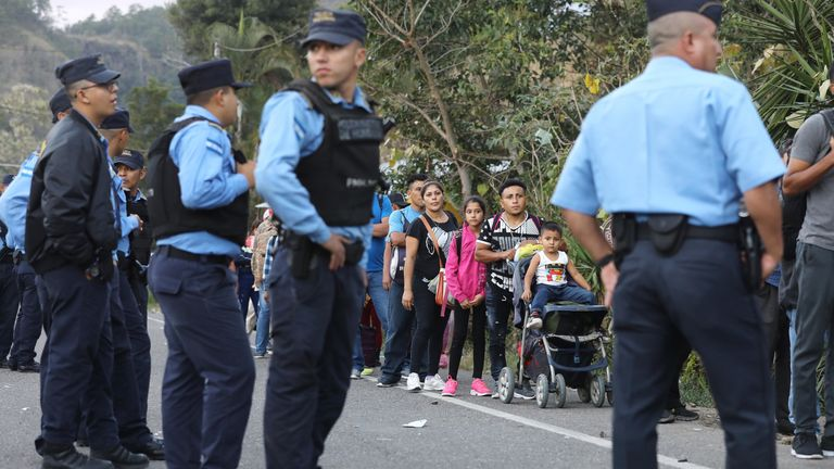 Police keep watch as Honduran migrants, part of a new 'migrant caravan,' wait in line to cross over the border checkpoint