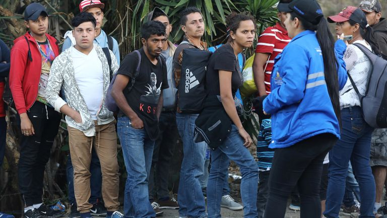 A migration official (2nd R) speaks to Honduran migrants, as they wait to cross the checkpoint