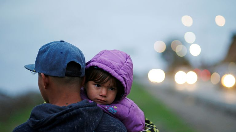 A man carries a little girl as part of the caravan