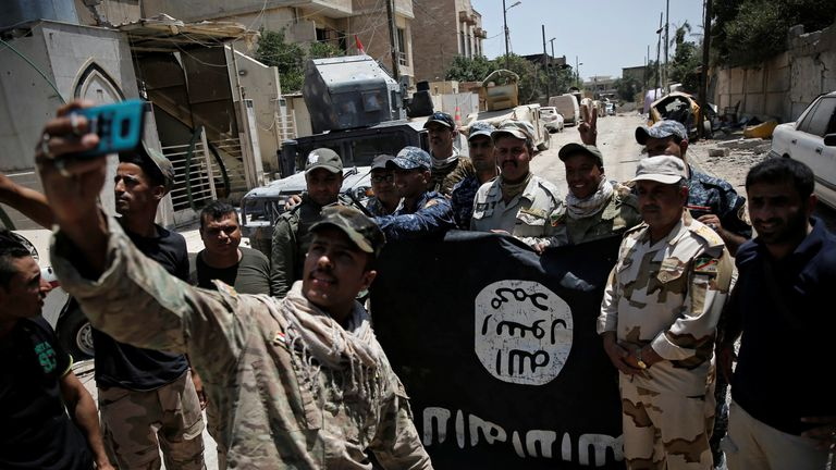 Members of the Iraqi Army with an Islamic State flag, after fighting militants in western Mosul in June 2017