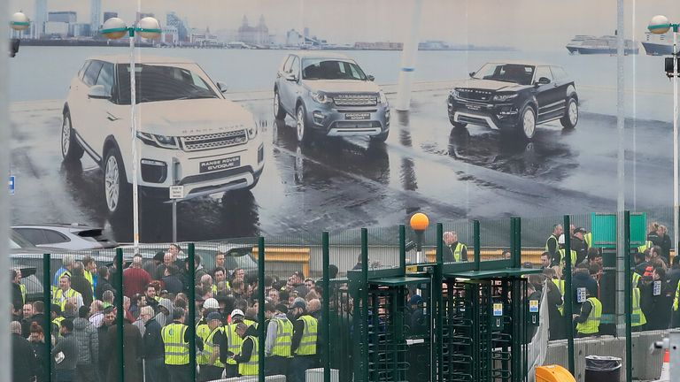 Staff gather outside the Jaguar Land Rover site in Halewood, Knowsley, Merseyside.