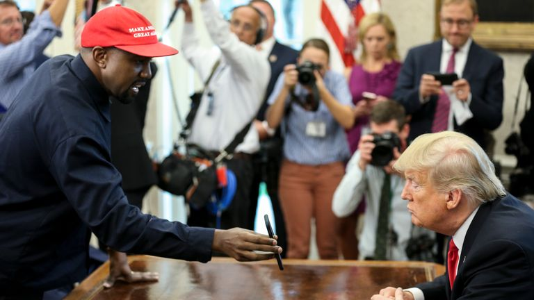 Rapper Kanye West , left, shows a picture of a plane on a phone to U.S. President Donald Trump during a meeting in the Oval office of the White House on October 11, 2018 in Washington, DC