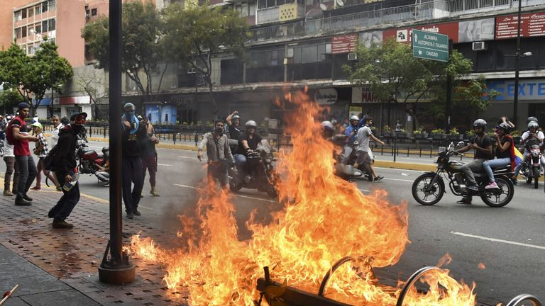 A protester burns a motorcycle during clashes with the security forces