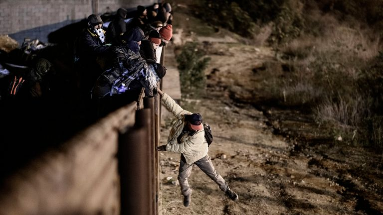 A migrant jumps the border fence to get into the US side to San Diego, California., from Tijuana