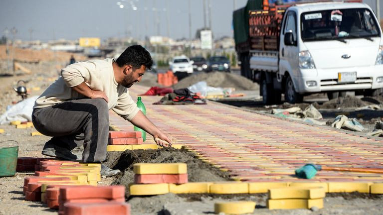 A worker lays paving stones for a pavement in east Mosul in November 2018, amid reconstruction efforts