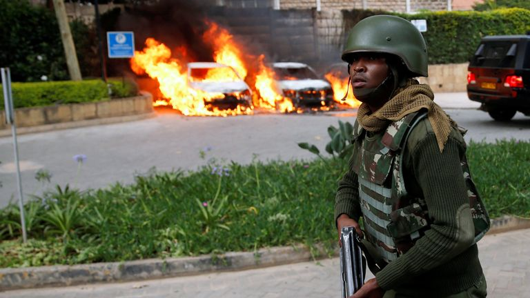 A policeman runs past burning cars at the scene where explosions and gunshots were heard at the Dusit hotel compound, in Nairobi
