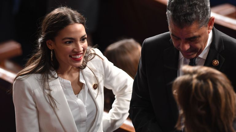 Rep. Alexandria Ocasio-Cortez, D-NY, chats to other representatives before the ceremony