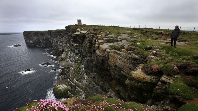 Visitors walk along the cliff tops high above the sea at Marwick Head in Orkney