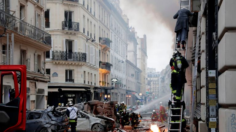 A woman is evacuated by firefighters from an apartment after anexplosion in a bakery