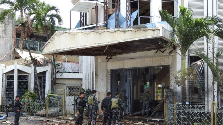 Policemen and soldiers stand outside bomb-hit church in Jolo, Sulu