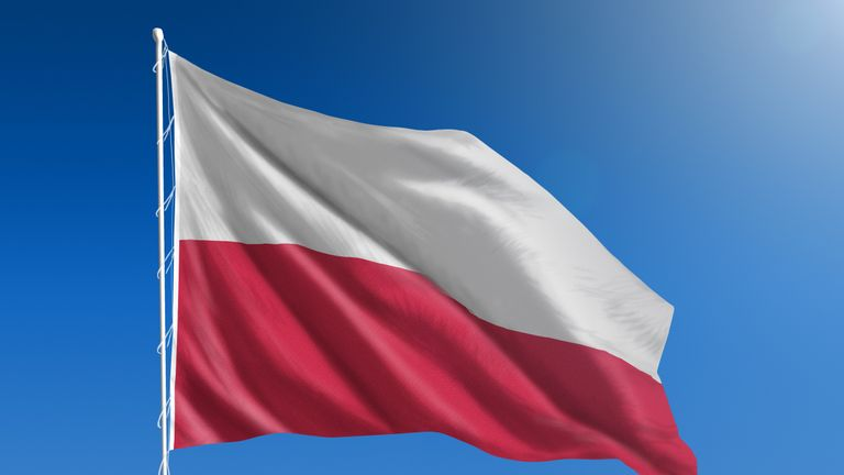 The National flag of Poland blowing in the wind in front of a clear blue sky