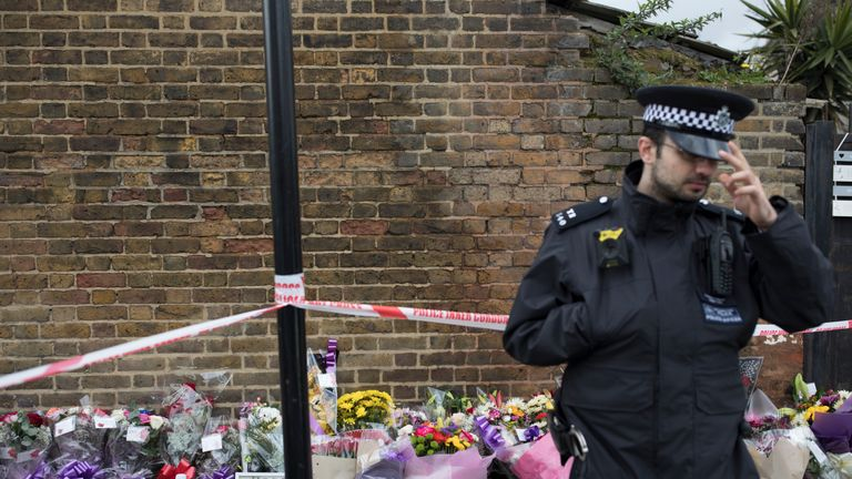 A Police Officer stands next to floral tributes at the scene where a 17 year old girl was shot and killed in Northumberland Park on April 4, 2018 in London, England