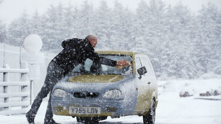 A man scrapes ice off the windscreen of a Robin Reliant in Cumbria