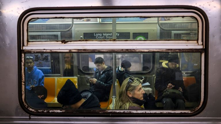 Passengers ride a train at Seventh Avenue subway station in New York