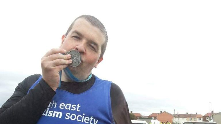 Shaun Hughes kisses his medal after completing the Great North Run in 2013