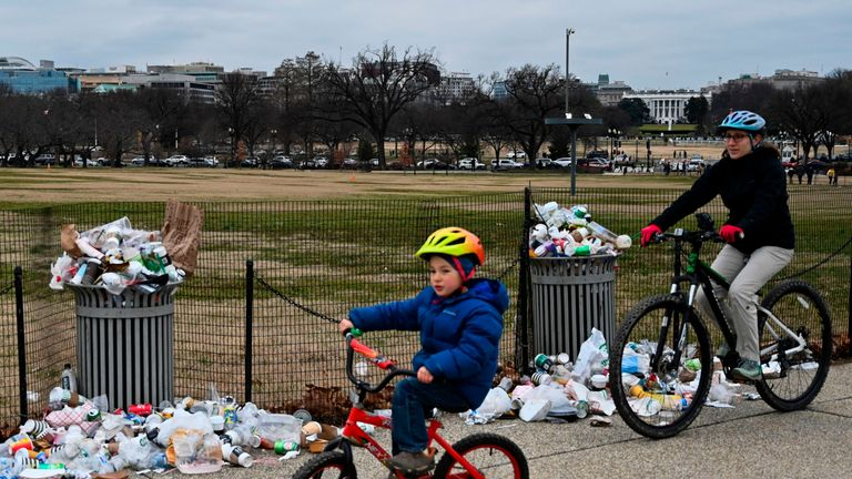The White House is seen in the background as people bike past trash uncollected on the National Mall, due to the partial shutdown of the US government on January 2, 2019 in Washington, DC