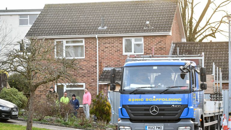 Contractors and military personnel wait outside the home as work begins