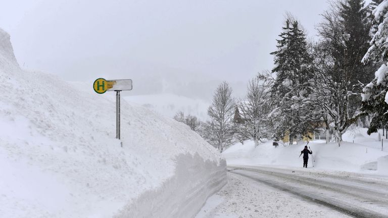 A skier walks past a bus stop after heavy snowfall in the small village of Filzmoos, Austria