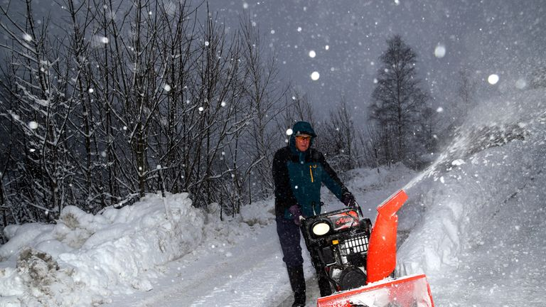 A man removes snow from a road during heavy snowfall in Eisenerz, Austria