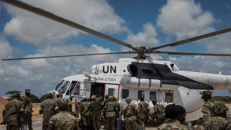 Members of the 17th Battle Group of the Uganda People's Defense Force (UPDF) serving in the African Union Mission in Somalia (AMISOM) load an United Nations helicopter outside of AMISOM's Forward Operating Base Barawe on October 10, 2016
