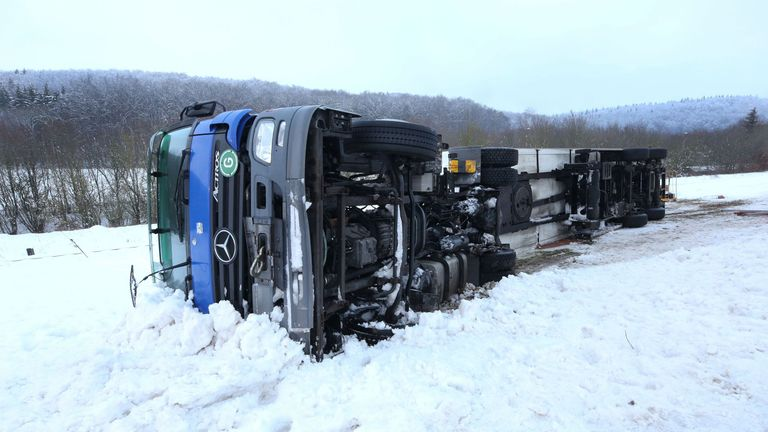An overturned lorry in the snow on a B road in Muensingen in southern Germany
