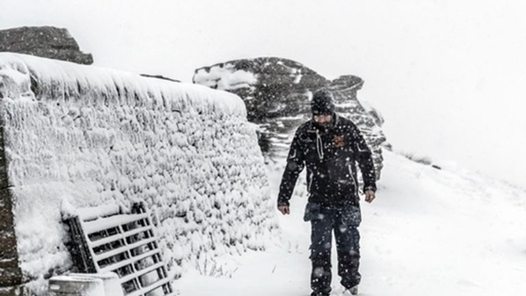 A walker trudges through the snow in Tan Hill in North Yorkshire