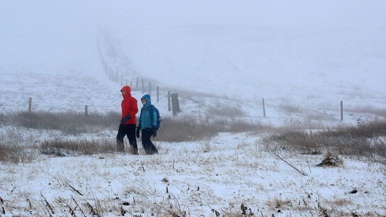 Walkers on a snow-covered path near Macclesfield, Cheshire