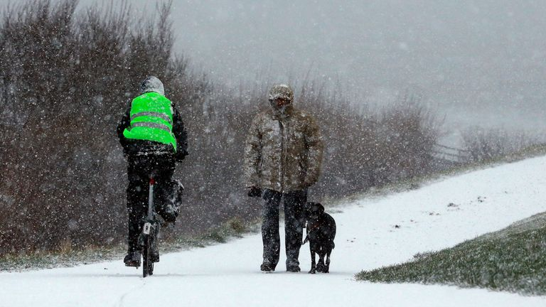 A man walks his dog through the snow in Whitley Bay, North Tyneside