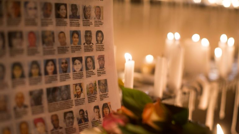 The photographs of the Westgate Shopping Centre victims are placed next to burning candles outside the Westgate Shopping Centre on September 28, 2013 in Nairobi, Kenya