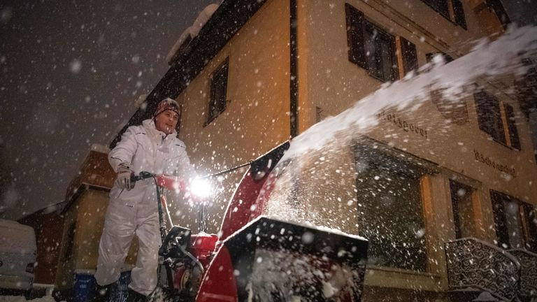 Rudolf Roeckenschuss uses a snow blower to clear his courtyard in Miesbach, southern Germany