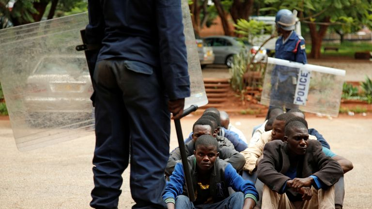 People arrested during protests wait to appear at a magistrates' court in Harare