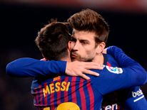 Lionel Messi (L) with Barcelona team-mate and Kosmos president Gerard Pique