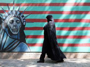 An Iranian woman walks past an anti-US mural