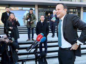 Ireland's Prime Minister Leo Varadkar (R) speaks to members of the media as he arrives at Dublin Castle