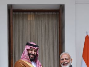 India's PM Narendra Modi (R) shakes hands with Saudi Crown Prince Mohammed bin Salman