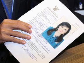 Thai Raksa Chart party leader Preechapol Pongpanich, holds up application of candidate for Prime Minister, Thailand's Princess Ubolratana Rajakanya Sirivadhana Barnavadi