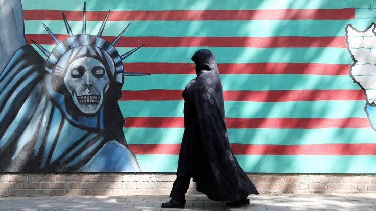 An Iranian woman walks past an anti-US mural