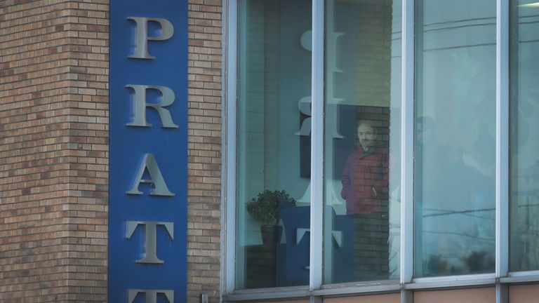 Workers look out an office window following a shooting at the Henry Pratt Company