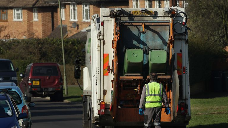 Refuse collectors empty green 'wheelie' bins