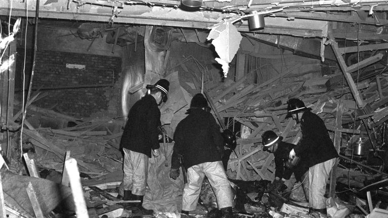Firemen searching through rubble in one of the pubs bombed in 1974