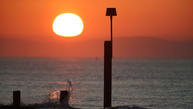 The sun rises over Boscombe beach in Dorset