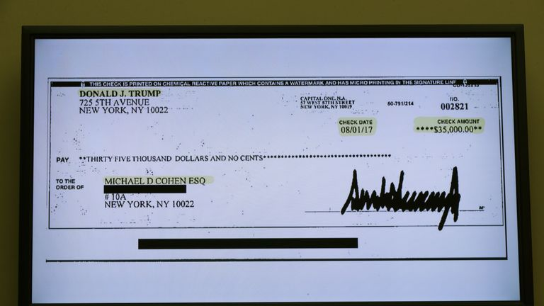 A copy of a cheque paid to Michael Cohen by President Trump is displayed as Michael Cohen, former attorney and fixer for President Donald Trump testifies before the House Oversight Committee on Capitol Hill February 27, 2019 in Washington, DC. Last year Cohen was sentenced to three years in prison and ordered to pay a $50,000 fine for tax evasion, making false statements to a financial institution, unlawful excessive campaign contributions and lying to Congress as pa