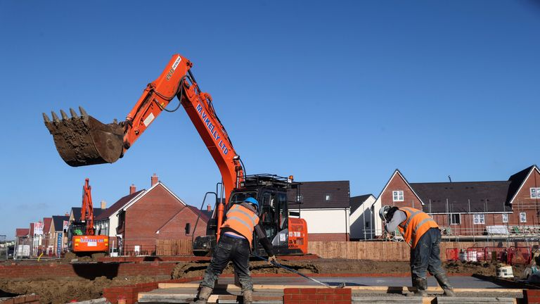 Construction workers work on a Taylor Wimpey housing estate in Aylesbury