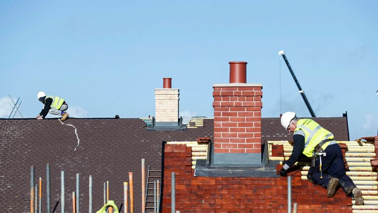 Construction workers work on a Taylor Wimpey housing estate