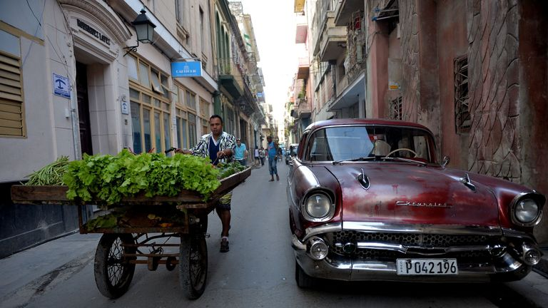 A fruit and vegetables vendor walks along a street of Havana